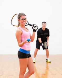 Woman & man racquetball players holding racquetball racquet, wearing racquetballglove, eyewear & wearing racquetball shoes.