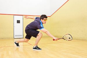 Squash player hitting squash ball with squash racket wearing squash shoes and squash goggles