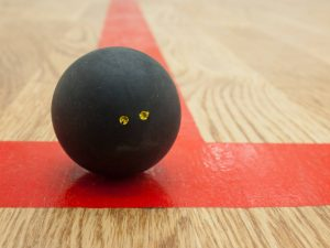 double dot squash ball on squash court