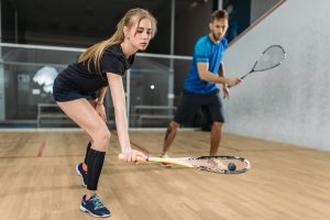 squash players playing squash on a squash court wearing squash clothing