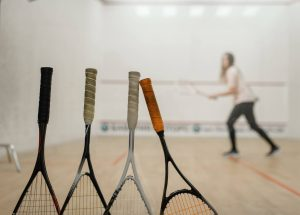 squash rackets on squash court with squash player hitting a squash ball