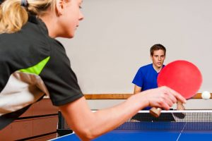 table tennis players playing with ping pong paddles, on a ping pong table and ping pong net